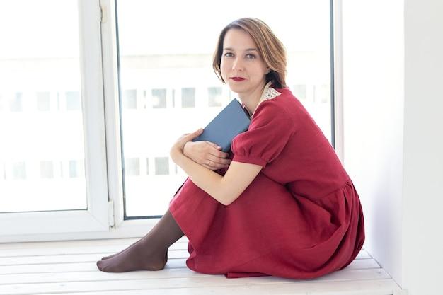 Portret van een mooi charmant jong meisje in een bescheiden rode jurk die een boek leest bij het raam.
