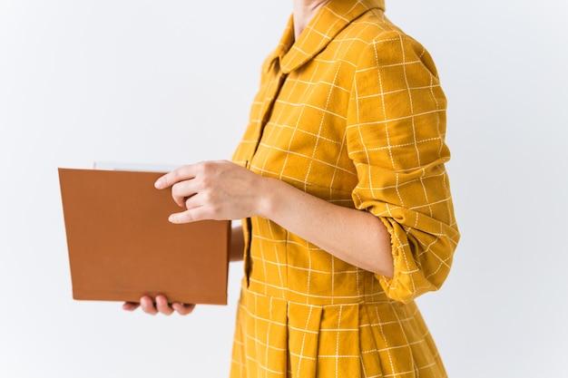 Portret van een mooi donkerbruin meisje in een gele retro jurk die een boek leest