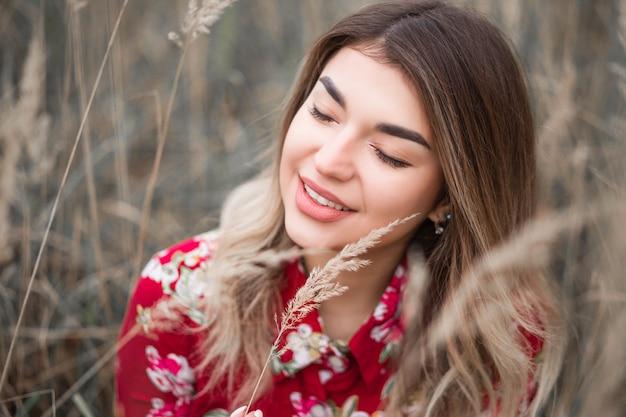 Portret van een mooi donkerbruin meisje onder het hoge gras