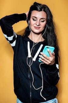 Portret van een mooi donkerbruin meisje, op een oranje achtergrond in een fiets en jeans, die naar muziek luistert