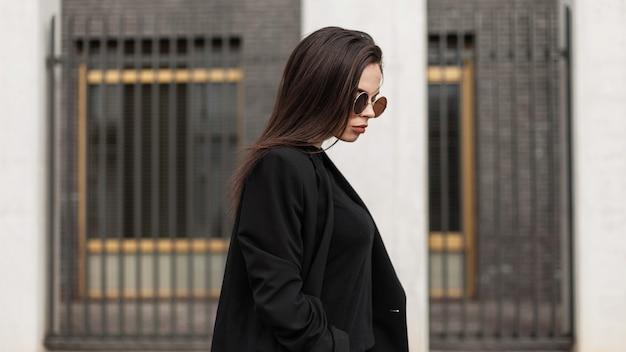 Portret van een mooi elegant meisje met zonnebril in zwarte formele kleding en een jas loopt door de stad