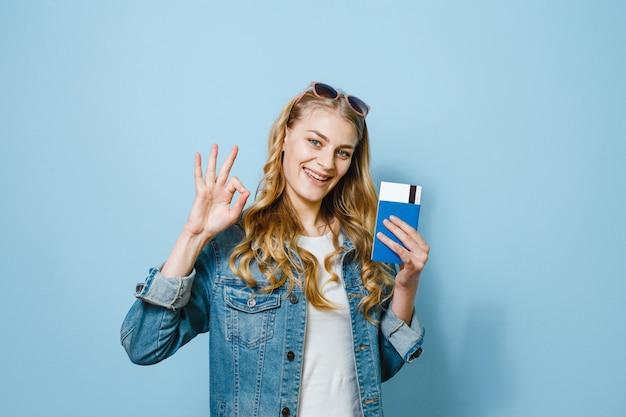 Portret van een mooi gelukkig meisje dat over de blauwe kaartjes en het paspoort van de achtergrondholdingsreis wordt geïsoleerd