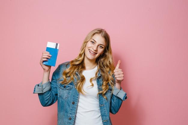 Portret van een mooi gelukkig meisje dat over de roze kaartjes en het paspoort van de achtergrondholdingsreis wordt geïsoleerd