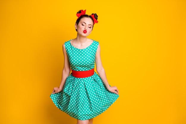 Portret van een mooi glamoureus dromerig meisje met een gestippelde groenblauwe jurk die je een luchtkus stuurt, geïsoleerd over een levendige gele kleurachtergrond