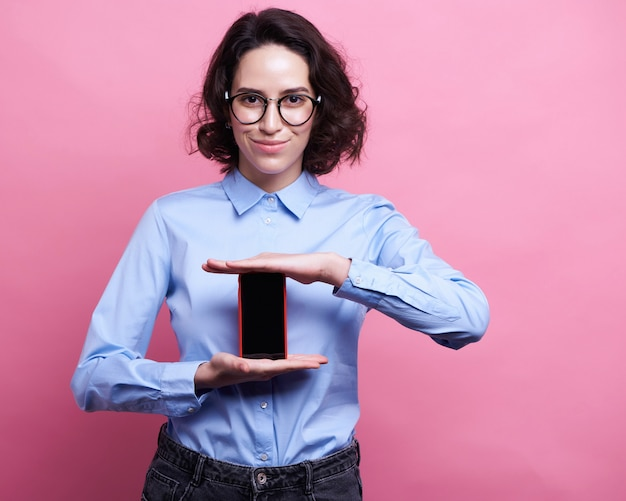 Portret van een mooi glimlachend meisje die mobiele telefoon met behulp van terwijl status geïsoleerd over roze achtergrond