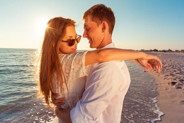 Portret van een mooi houdend van paar dat pret heeft bij het strand