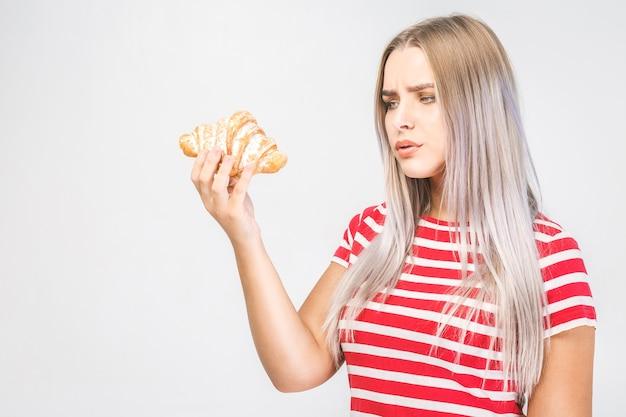 Portret van een mooi jong blond geschikt meisje dat een rode bovenkant draagt die een croissant in haar handen houdt die het droevig bekijkt, geïsoleerd op een witte achtergrond.