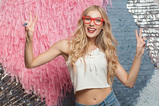 Portret van een mooi jong blond meisje met een vredesteken en een brede glimlach