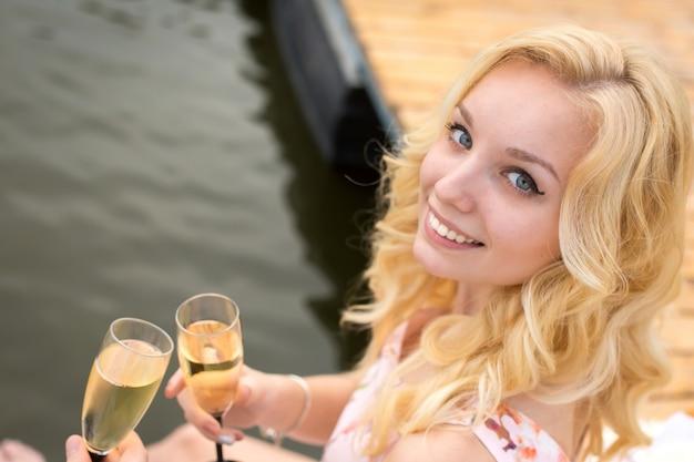 Portret van een mooi jong blondemeisje met een glas champagne