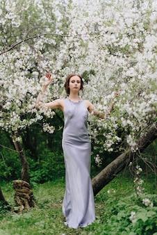 Portret van een mooi jong dun wit meisje op een lentekersenbloesem 1