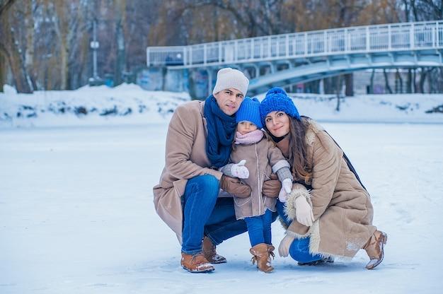 Portret van een mooi jong gezin in beige en blauwe kleren op de achtergrond van een bevroren meer in het park
