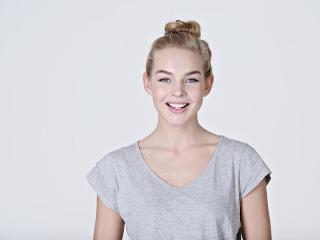Portret van een mooi jong lachend meisje. vrouwelijk gezicht met brede glimlach. aantrekkelijk blond meisje met zich meebrengt in de studio in een casual grijs t-shirt