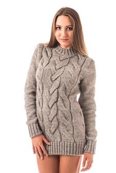 Portret van een mooi jong meisje dat een gebreide trui draagt die in studio op een witte muur stelt