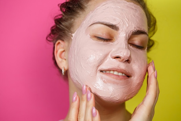 Portret van een mooi jong meisje dat een verfrissend masker op haar gezicht zet om de huid te verjongen en te versterken. schoonheidsbehandelingen