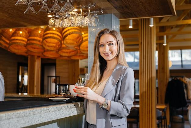 Portret van een mooi jong meisje die heerlijke koffie drinkt in een mooi modern café.