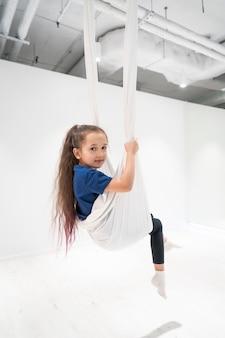 Portret van een mooi jong meisje die zich bezighouden met vlieg yoga op doeken.