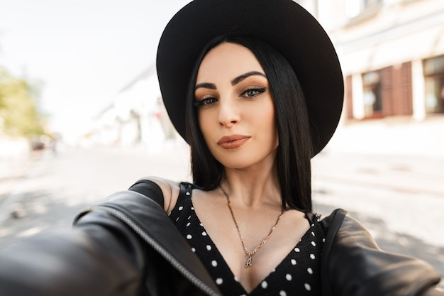Portret van een mooi jong meisje in modieuze bovenkleding met een leren jas en een hoed loopt door de stad en maakt een selfie Premium Foto