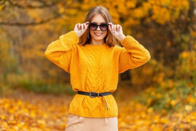 Portret van een mooi jong meisje met een schattige glimlach in een vintage gebreide gele trui kijkt door een modezonnebril naar de camera in een herfstpark met helder kleurrijk gouden blad.