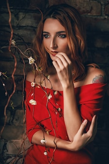 Portret van een mooi jong meisje met rood haar in een rode jurk.
