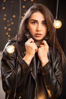 Portret van een mooi jong model in zwart lederen jas poseren in de buurt van lampen.