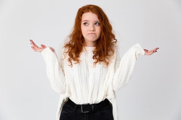 Portret van een mooi jong roodharig meisje dat zich geïsoleerd over witte achtergrond bevindt, schouders ophaalt
