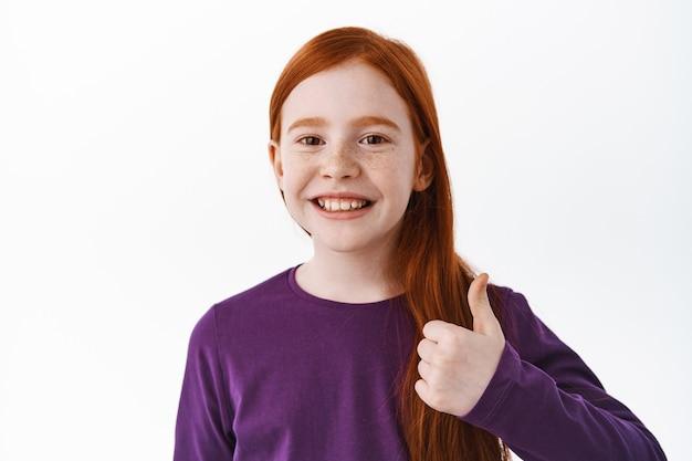 Portret van een mooi jong roodharig meisje, een kind uit de eerste klas toont duimen omhoog en glimlacht tevreden, zeg ja, vind het leuk en keur het goed, prees, staande over de witte muur