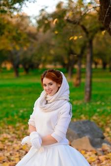Portret van een mooi jong roodharig meisje met bloemen ziet er aantrekkelijk uit in een witte jurk