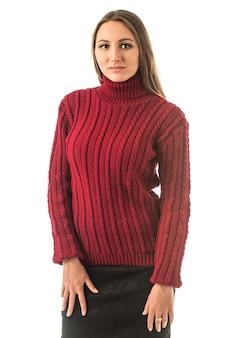 Portret van een mooi jong slank meisje in een rode gebreide trui poseren op een witte muur in de studio