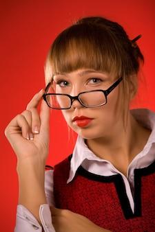 Portret van een mooi jong studentenmeisje dat in glazen de camera op een rode achtergrond bekijkt