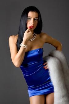 Portret van een mooi jong vrouwenmodel dat een blauwe jurk draagt die zich voordeed op een grijze achtergrond in de studio. concept van vrouwelijke stijlvolle stijlvolle make-up en imago. reclame dameskleding concept