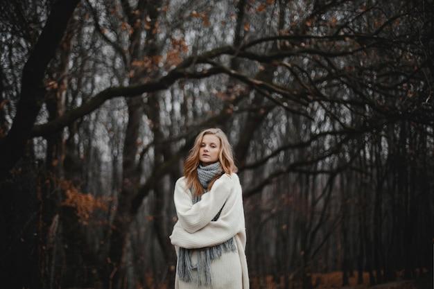 Portret van een mooi kaukasisch blond meisje gekleed in een witte trui, alleen krullend in het herfstbos