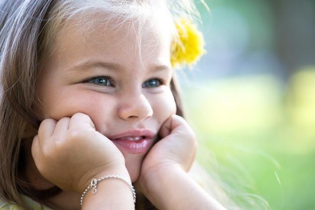 Portret van een mooi kindmeisje met een blije gezichtsuitdrukking die buiten lacht en geniet van een warme zonnige zomerdag.