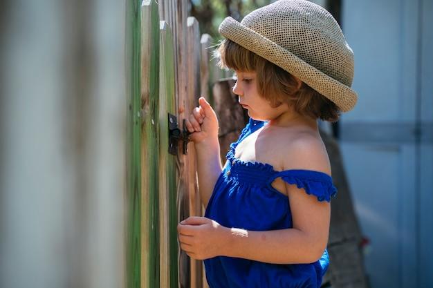 Portret van een mooi klein blondemeisje bij de huistuin