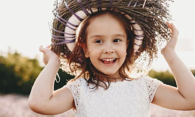 Portret van een mooi klein meisje close-up lachen terwijl het zetten van een kroon van bloemen op het hoofd tegen zonsondergang in een veld met bloemen.
