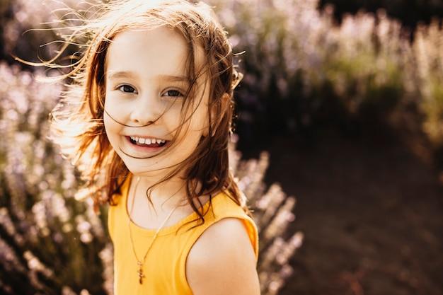 Portret van een mooi klein meisje dat camera bekijkt die lacht terwijl ze in een veld met bloemen tegen zonsondergang gekleed in geel.
