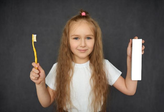 Portret van een mooi klein meisje dat lacht met een tandenborstel en een witte doos tandpasta