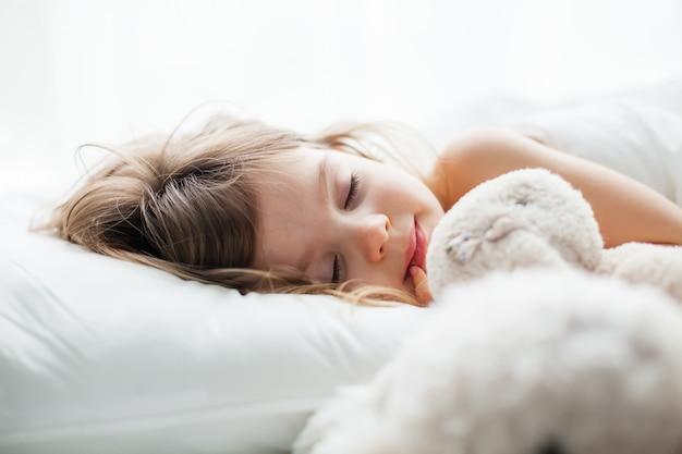 Portret van een mooi klein meisje dat zoet in een wit bed slaapt