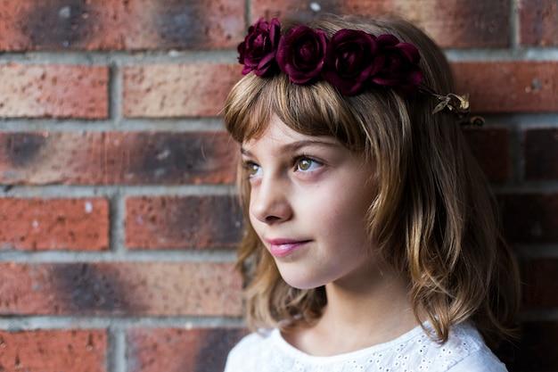 Portret van een mooi klein meisje draagt een rode krans rozen op haar hoofd. lifestyle