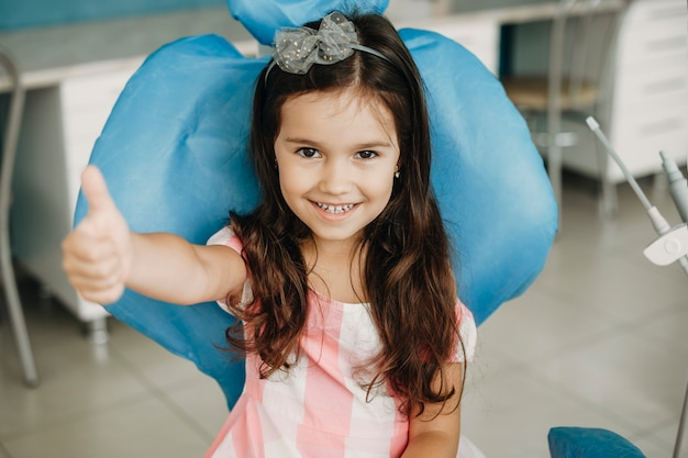Portret van een mooi klein meisje duim opdagen na een tandoperatie. gelukkig kind na tandonderzoek in een pediatrische stomatologie.