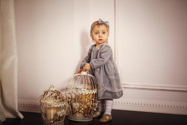 Portret van een mooi klein meisje in een grijze jurk. kopieer ruimte.