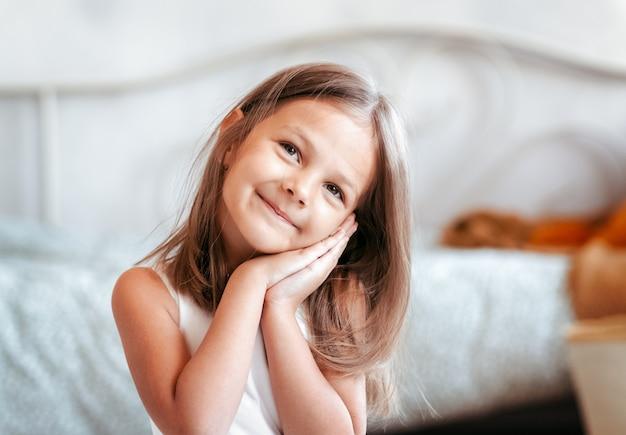 Portret van een mooi klein meisje in een lichte kamer. gelukkige jeugd