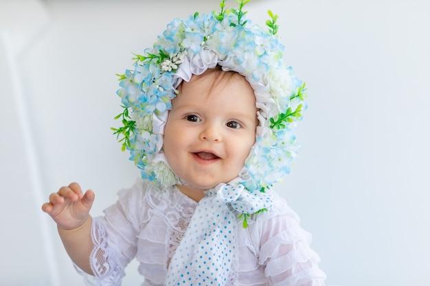 Portret van een mooi klein meisje in een lichte kamer in een hoed gemaakt van bloemen