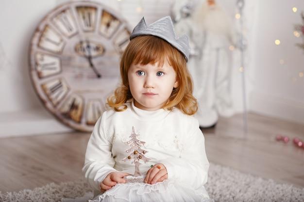 Portret van een mooi klein meisje in een witte jurk en een kroon in het interieur met kerstversiering. kleine prinses