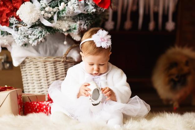 Portret van een mooi klein meisje in een witte jurk en wikkel haar met een bloem in het interieur met kerstversiering