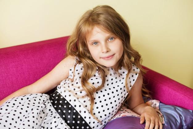 Portret van een mooi klein meisje in polka dot jurk close-up rustend op paarse sofa