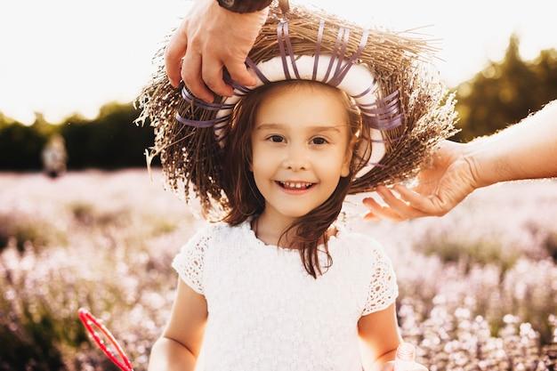 Portret van een mooi klein meisje kijken camera glimlachen buiten terwijl haar vader een kroon van bloemen zet in een bestand d van bloemen.