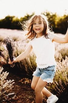 Portret van een mooi klein meisje kijken camera lachen tijdens het spelen in een veld van ecologische bloemen tegen zonsondergang.