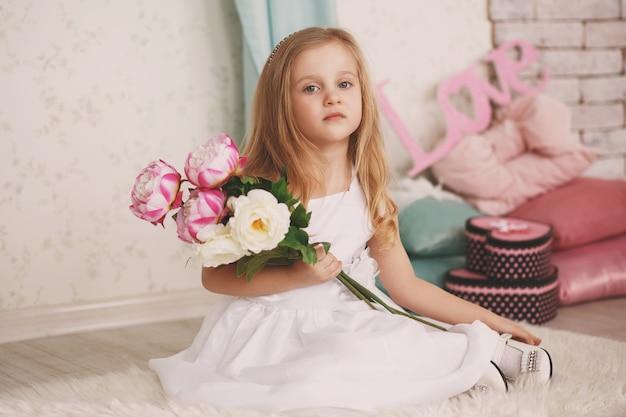 Portret van een mooi klein meisje met bloemen