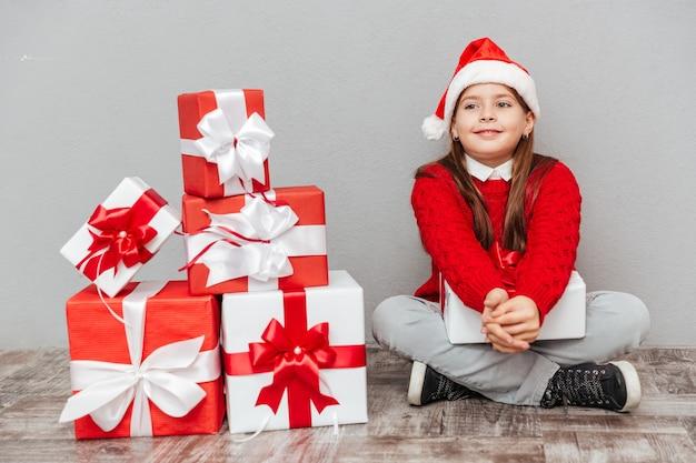 Portret van een mooi klein meisje met een kerstmuts die in de buurt van geschenkdozen zit