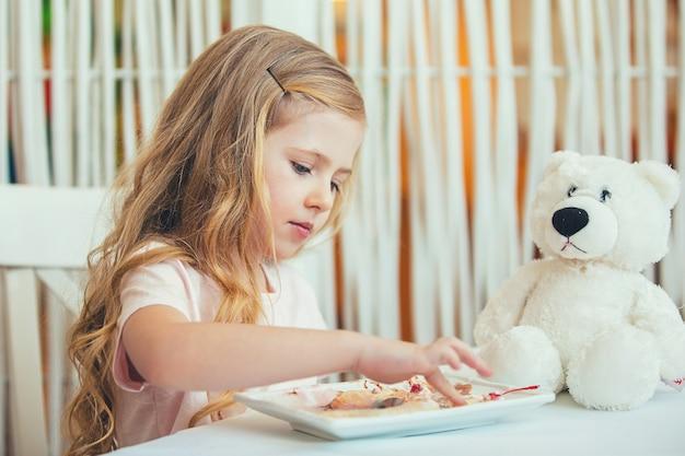 Portret van een mooi klein meisje met een teddybeer in een café dat een heerlijk ijsje eet.